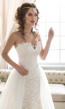 Потрясающее свадебное платье с кружевной отделкой, дополненное пышной верхней юбкой.