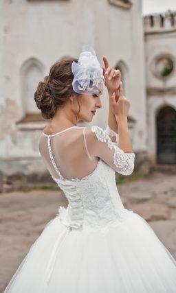 Закрытое свадебное платье с романтичным многослойным низом и длинными прозрачными рукавами.