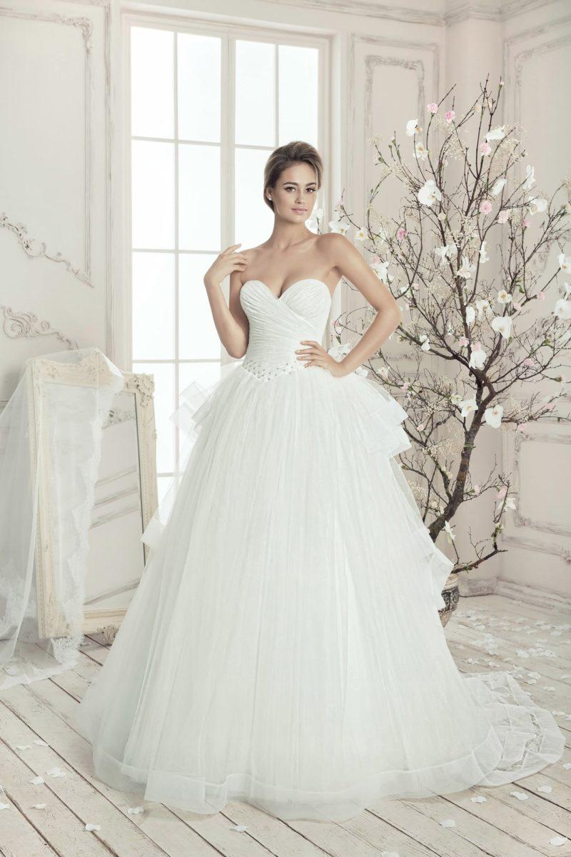 Открытое свадебное платье с драпировками на корсете и многоуровневым пышным шлейфом.