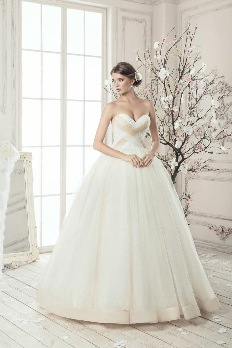 Нежное свадебное платье с открытым корсетом, украшенным бежевыми драпировками.