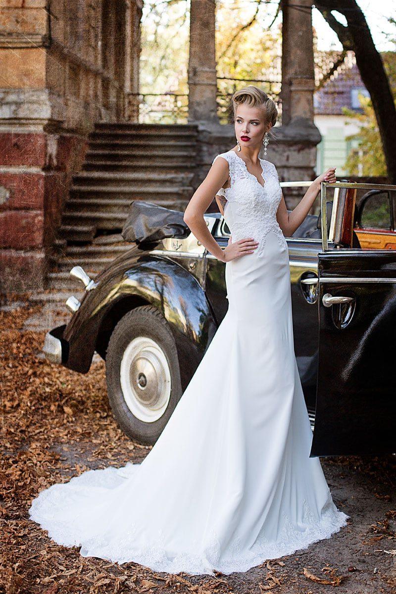 Элегантное свадебное платье с необычным вырезом на спинке и прямой юбкой со шлейфом.