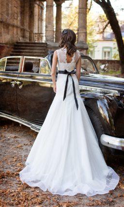Свадебное платье облегающего кроя из фактурной ткани, дополненное цветным поясом из атласа.