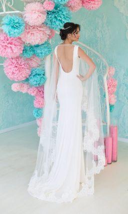 Изысканное свадебное платье прямого кроя с округлым вырезом спереди и смелым декольте сзади.