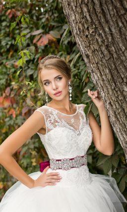 Роскошное свадебное платье с многослойной юбкой и закрытым верхом, дополненным цветным поясом.