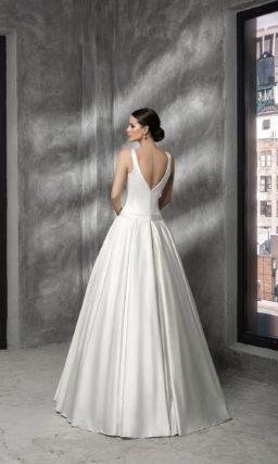 Атласное свадебное платье с заниженной талией, округлым декольте и бантом на поясе.