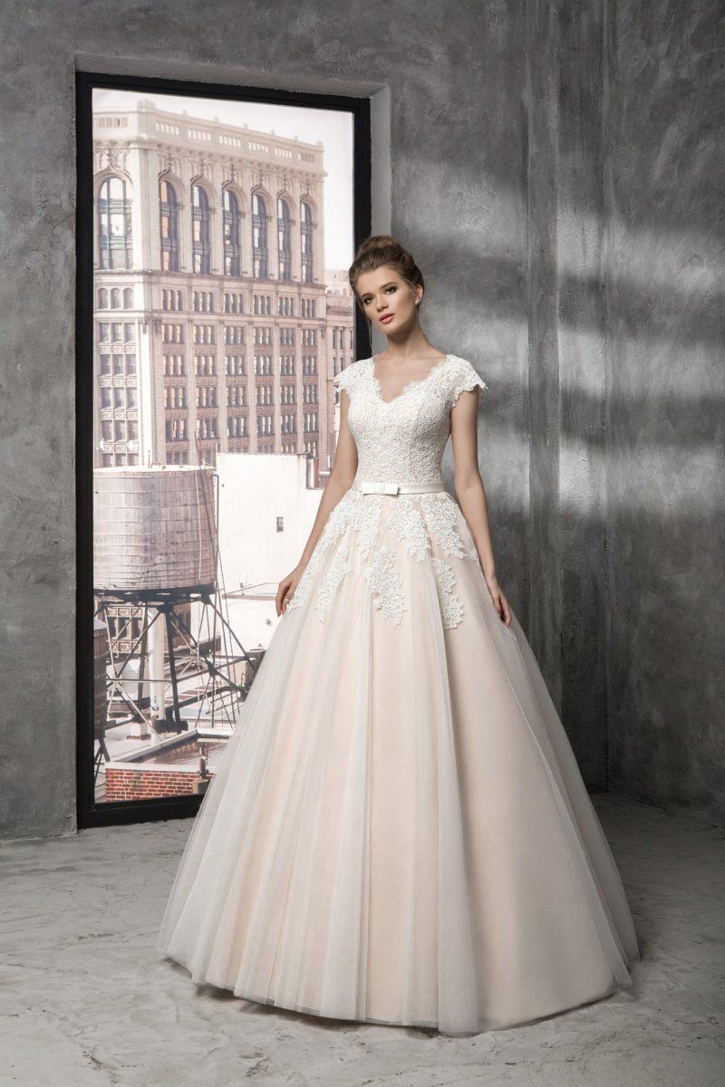 Пудровое свадебное платье с пышной юбкой и покрытым аппликациями закрытым верхом.