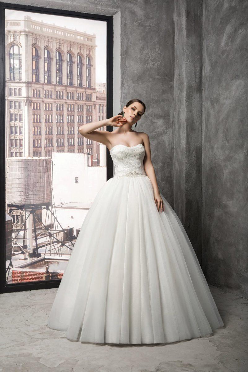 Свадебное платье с открытым лифом, украшенным вышивкой, и воздушной многослойной юбкой.
