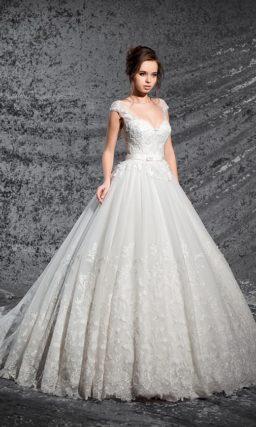 Кружевное свадебное платье с широкими полупрозрачными бретелями и пышной юбкой.