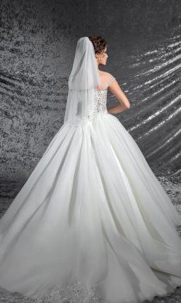 Притягательное свадебное платье пышного кроя с вертикальной полосой бисерного декора по юбке.