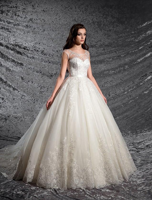 Нежное свадебное платье пышного кроя с закрытым лифом и узким атласным поясом на талии.