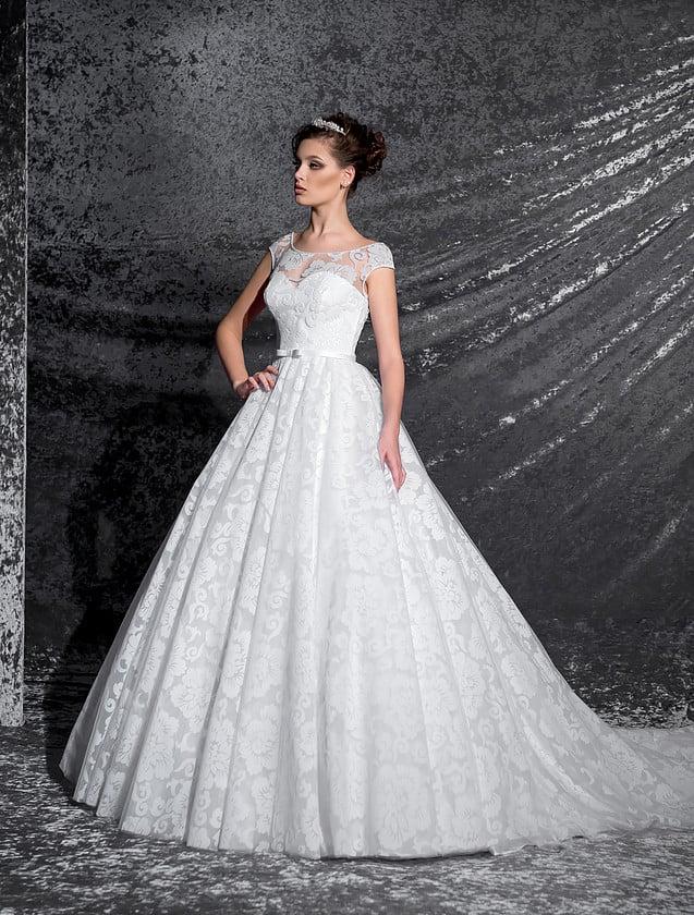 Романтичное свадебное платье пышного кроя с кружевным декором и узким поясом на талии.