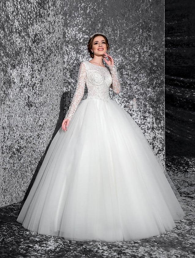 Утонченное свадебное платье с многослойной юбкой и кружевным декором лифа с длинным рукавом.