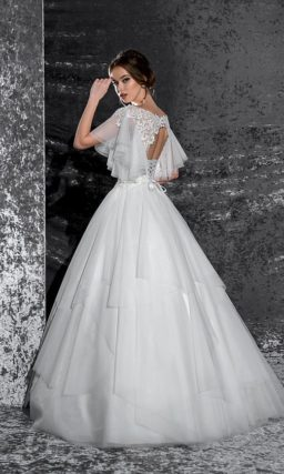 Стильное свадебное платье с многослойным низом и широкими полупрозрачными рукавами.