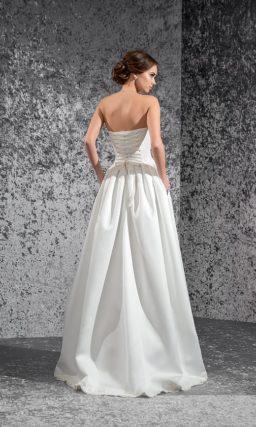 Сияющее свадебное платье пышного кроя с открытым лифом и стильным фактурным декором.