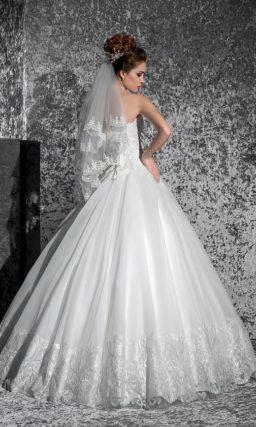 Открытое свадебное платье с лифом в форме сердца, украшенным кружевом, и пышным подолом.