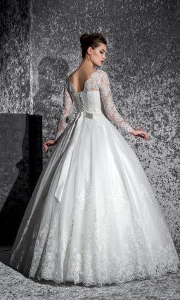 Закрытое свадебное платье с длинными рукавами и кружевной отделкой по низу пышной юбки.