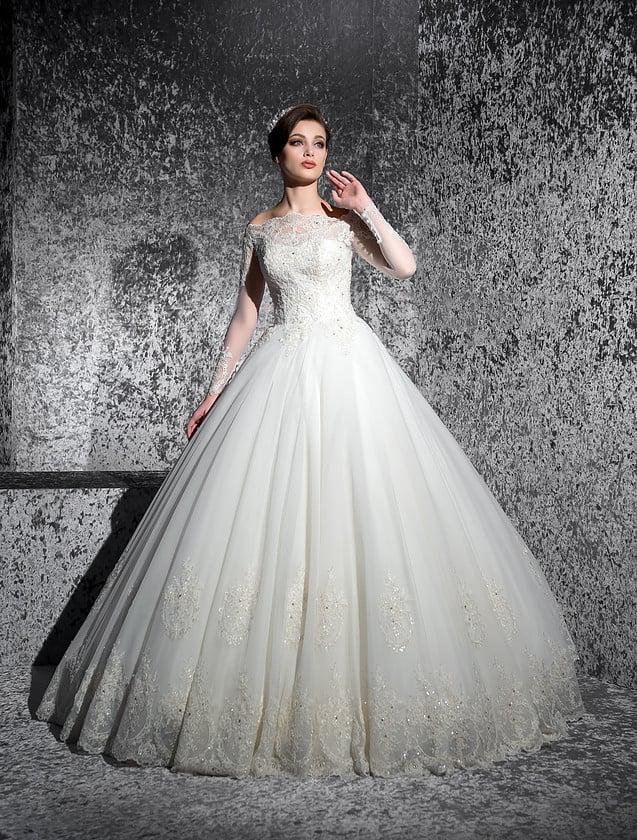 Женственное свадебное платье с фигурным вырезом, открывающим плечи, и пышной юбкой.