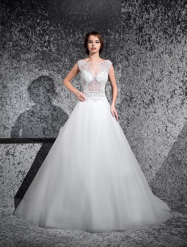 Свадебное платье с многослойным подолом и полупрозрачным верхом с вырезом лодочкой.
