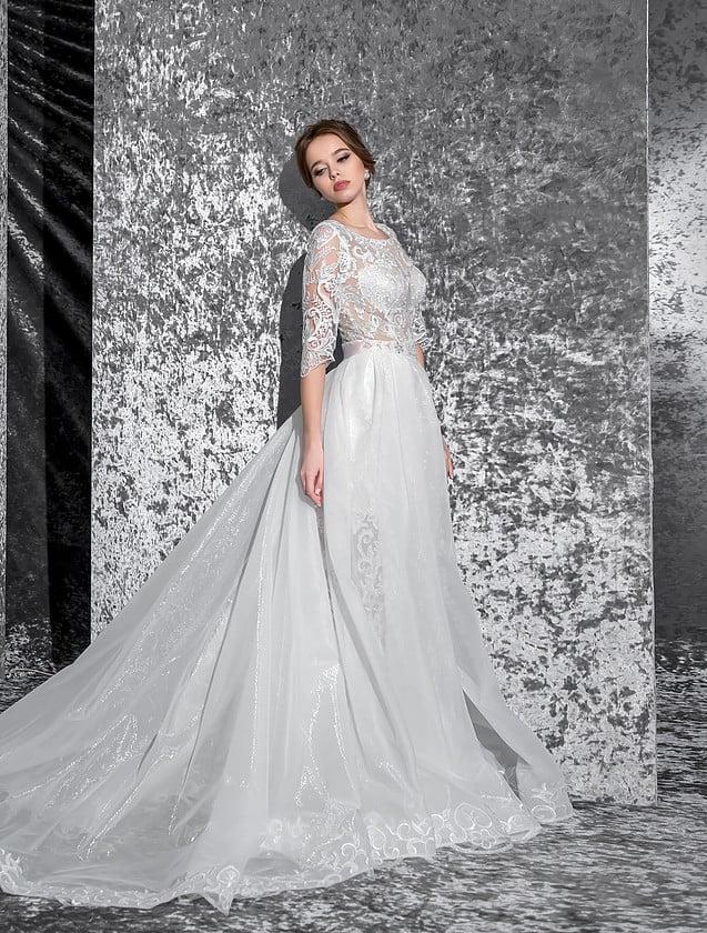 Романтичное свадебное платье прямого кроя с кружевным верхом и полупрозрачной многослойной юбкой.