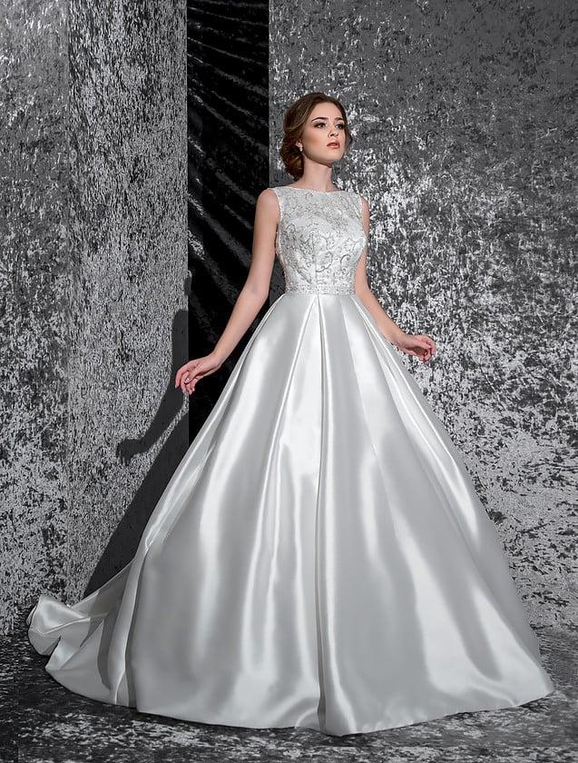 Пышное свадебное платье с шикарной атласной юбкой и деликатным закрытым верхом.