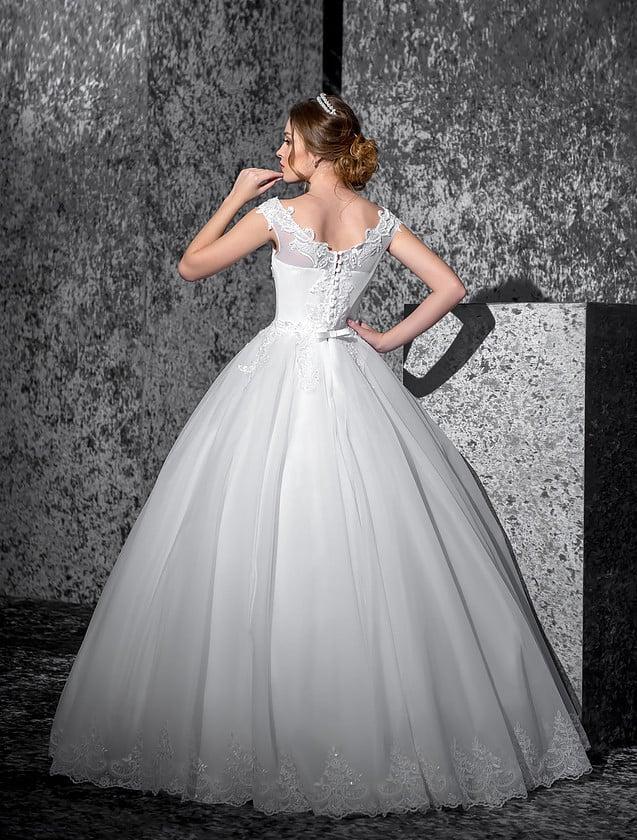 Пышное свадебное платье с округлым декольте с кружевным краем и аппликациями по юбке.