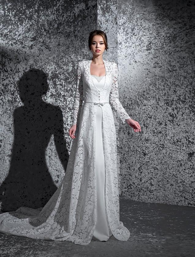 Впечатляющее свадебное платье из атласа, дополненное длинной кружевной накидкой с рукавом.