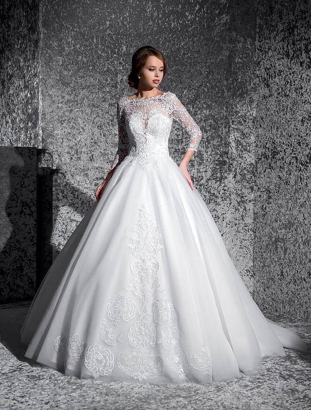 Торжественное свадебное платье с облегающими рукавами длиной три четверти и кружевным декором.