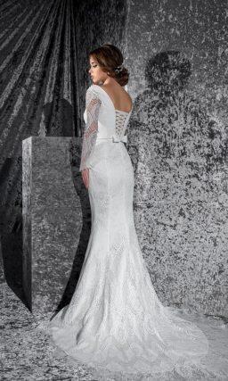 Прямое свадебное платье из ажурной ткани, с высоким вырезом и длинными рукавами.