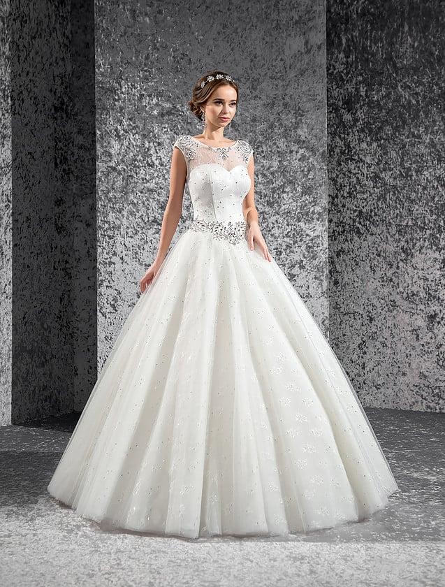 Торжественное свадебное платье с прозрачной тканью над корсетом и сияющей вышивкой бисером.