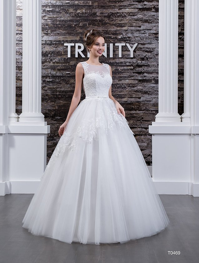 Закрытое свадебное платье с пышным силуэтом, украшенное кружевом по объемному подолу.