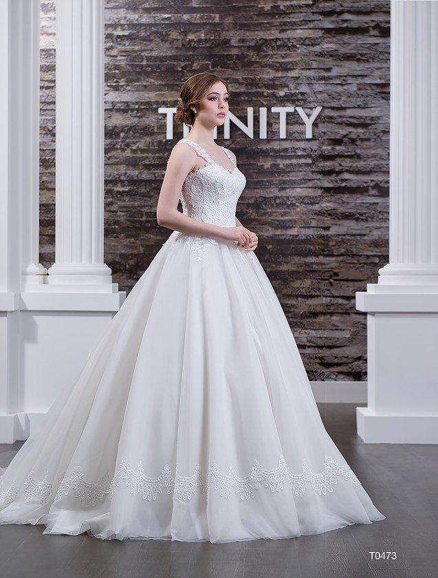 Свадебное платье с пышным подолом и кружевными бретелями над открытым лифом.
