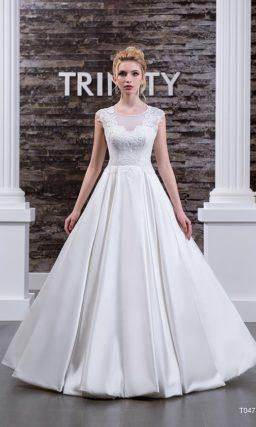 Атласное свадебное платье с полупрозрачной вставкой над корсетом и кружевной отделкой.