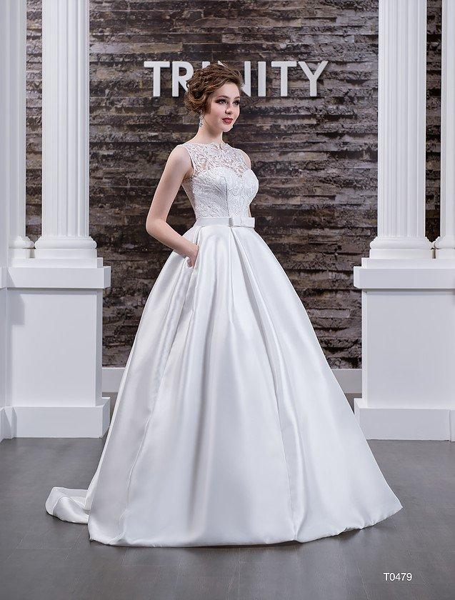 Закрытое свадебное платье с карманами в пышной атласной юбке и изящным поясом.