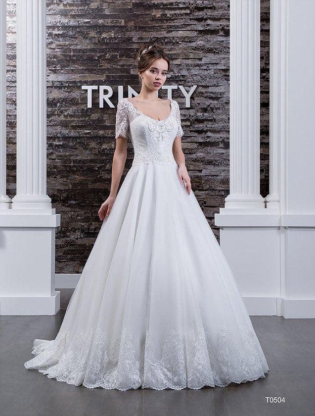Свадебное платье с округлым декольте и многослойной юбкой с кружевом по низу подола.