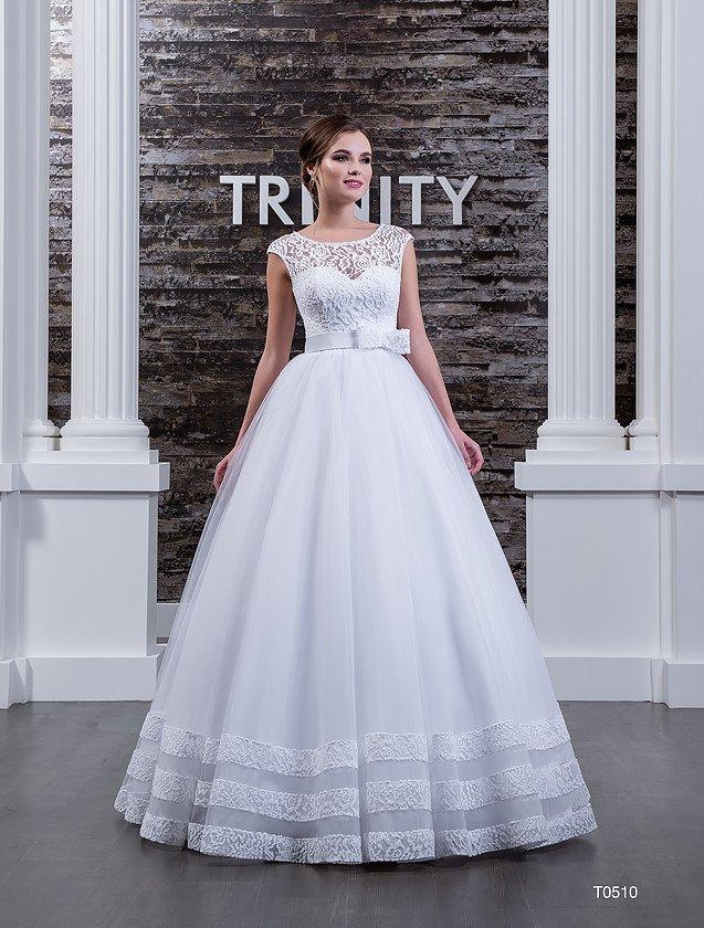 Свадебное платье с округлым вырезом, изящным поясом с бантом и романтичной отделкой подола.