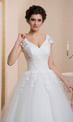 Пышное свадебное платье с глубоким V-образным вырезом и кружевной отделкой по корсету.