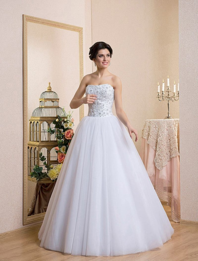 Великолепное свадебное платье с лаконичной пышной юбкой и открытым сияющим корсетом.