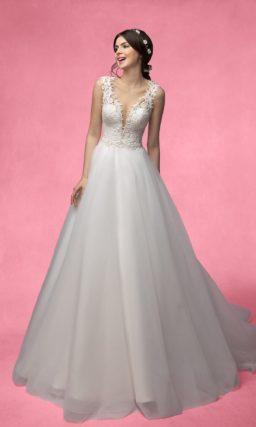 Пышное свадебное платье с глубоким вырезом, украшенным кружевной тканью.