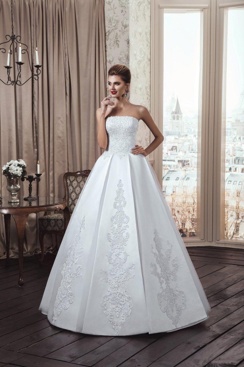 Великолепное свадебное платье пышного кроя из глянцевого атласа, украшенное кружевом.