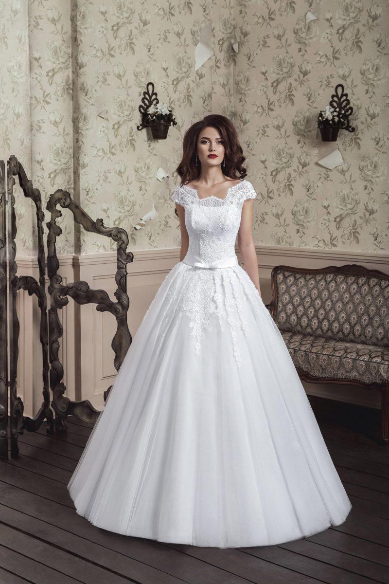 Нежное свадебное платье с небольшим фигурным декольте и многослойной пышной юбкой.