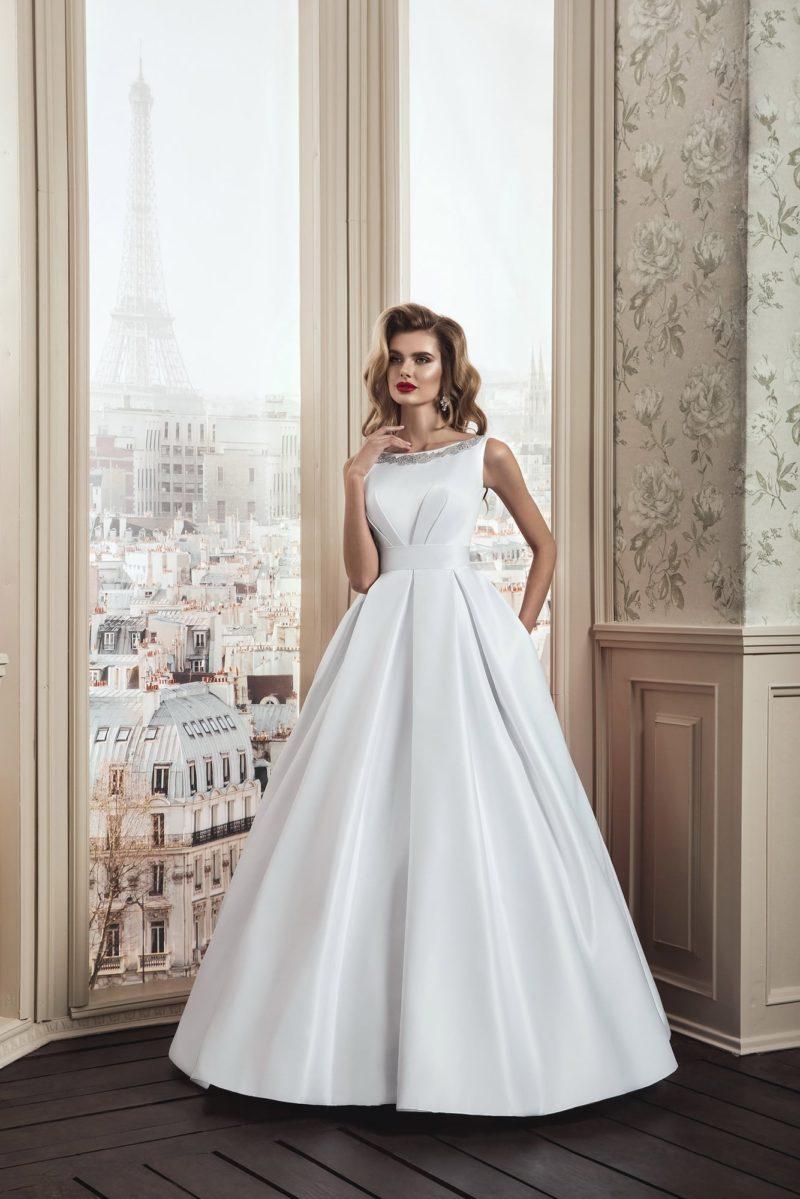 Стильное свадебное платье с вырезом «лодочка» и скрытыми сверху подола карманами.