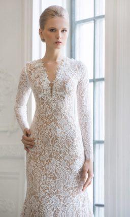 Прямое свадебное платье с бежевой подкладкой под белым кружевом, дополненное длинным рукавом.