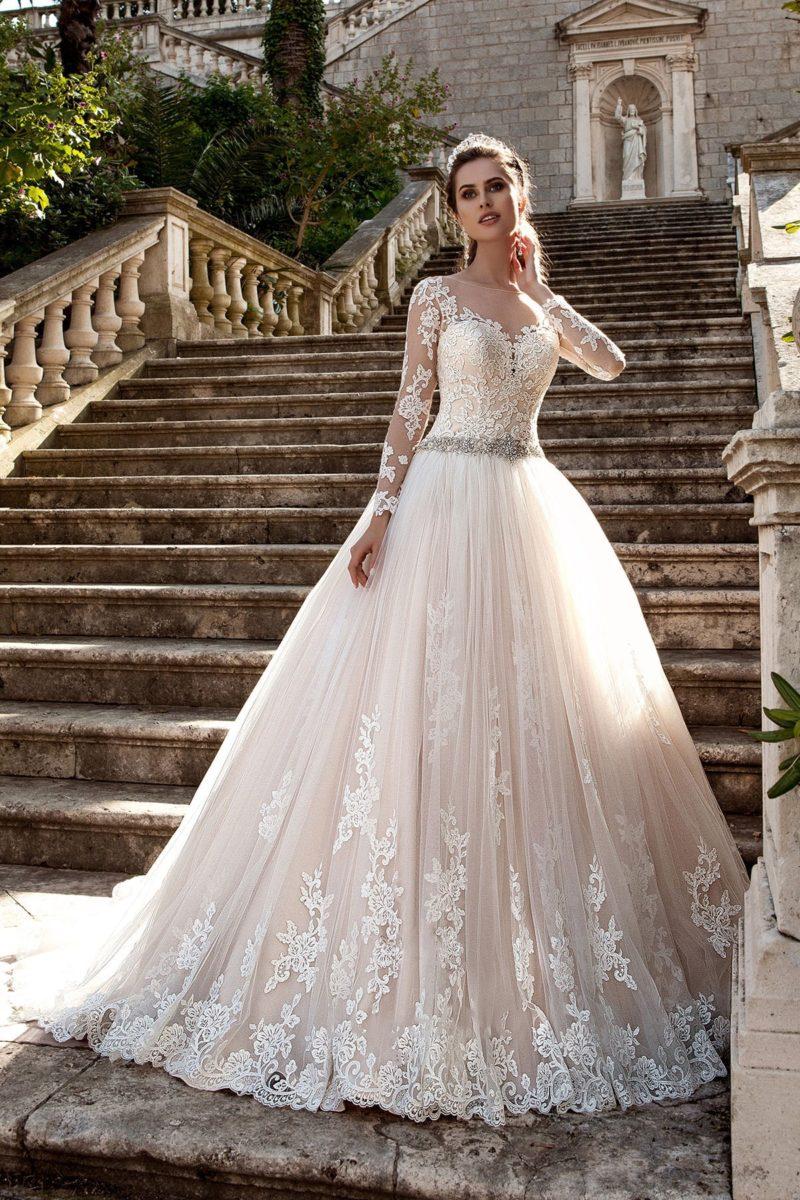 Свадебное платье с бисерным поясом, длинными рукавами из кружева и пышным низом.
