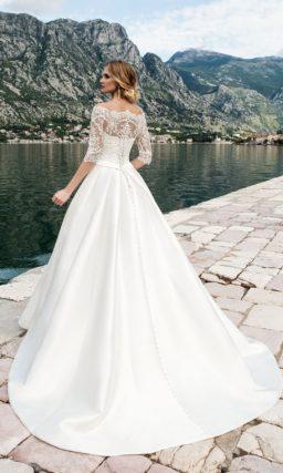 Роскошное свадебное платье с фигурным портретным декольте и рукавами из кружевной ткани.
