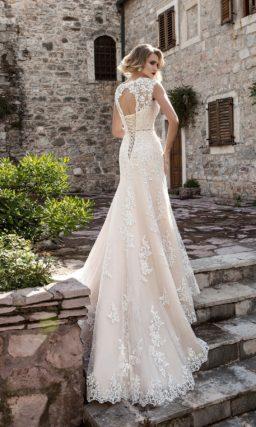 Бежевое свадебное платье с вырезом под горло, узким поясом с бантом на талии и кружевным декором.