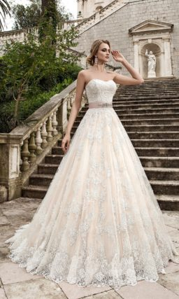 Пудровое свадебное платье пышного кроя с кружевным декором и розовым поясом с вышивкой.