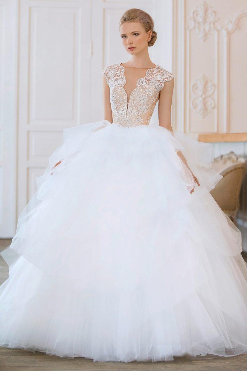 Изысканное свадебное платье с подчеркнуто пышной юбкой и глубоким декольте.