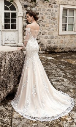 Свадебное платье кремового цвета, с кружевной отделкой и полупрозрачной спинкой.
