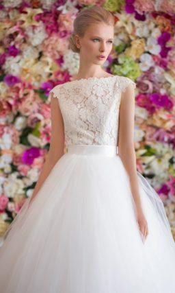 Пышное свадебное платье с атласным поясом и закрытым вырезом, оформленным кружевом.