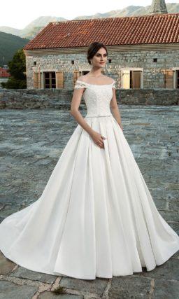 Шикарное свадебное платье с атласной юбкой и оформленным кружевом портретным декольте.